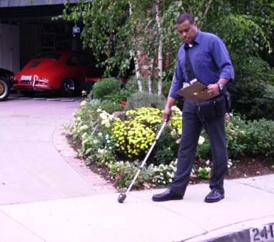 Darius measuring sidewalk in front of house